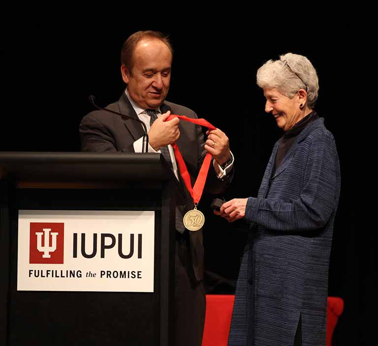 Patricia Biddinger receivers her 50th Anniversary Chancellor's Medallion from IUPUI Chancellor Nasser H. Paydar.
