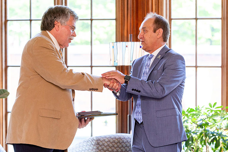 Michael Patcher receives his Chancellor's Medallion from Chancellor Nasser H. Paydar.