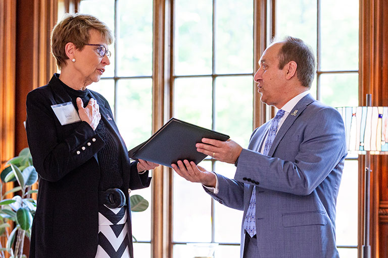 Rebecca Porter receives her Chancellor's Medallion from Chancellor Nasser H. Paydar