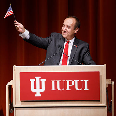 Chancellor Paydar waves the American flag he received during his naturalization ceremony.