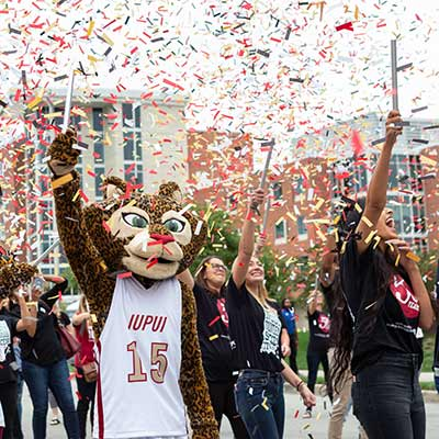 Jazzy the Jaguar mascot throws confetti as the kickoff for the Talent Showcase.