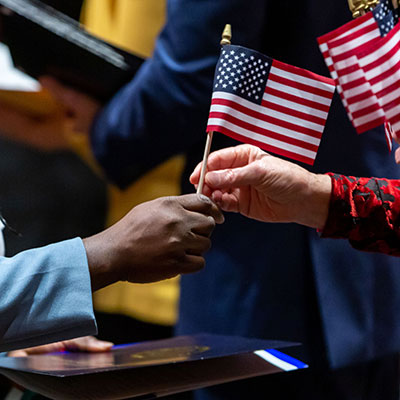 A new citizen is handed an American flag.
