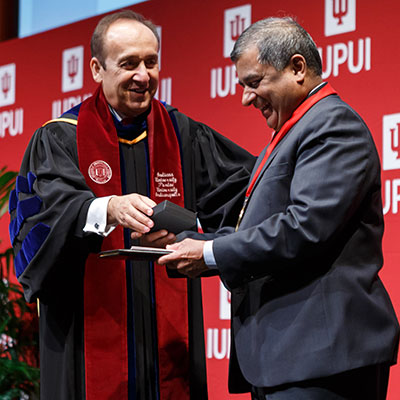 Former IUPUI Executive Vice Chancellor Uday Sukhatme receives his 50th Anniversary Chancellor's Medallion from Chancellor Nasser Paydar.