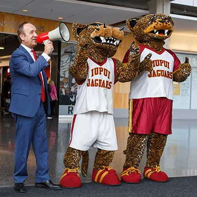 Chancellor Paydar shouts in a megaphone with the Jaguar mascots.