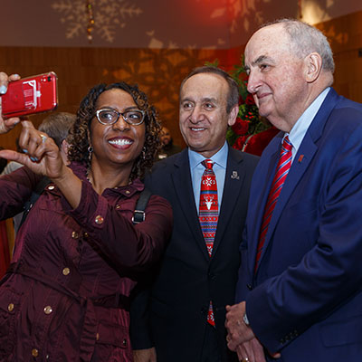 An IUPUI employee takes a selfie with Chancellor Nasser H. Paydar and IU President Michael A. McRobbie at the 2019 Holiday Open House.