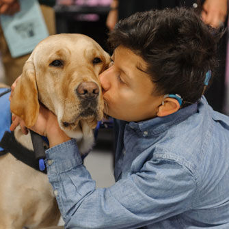 A little boy kisses his ICAN service dog on the cheek.