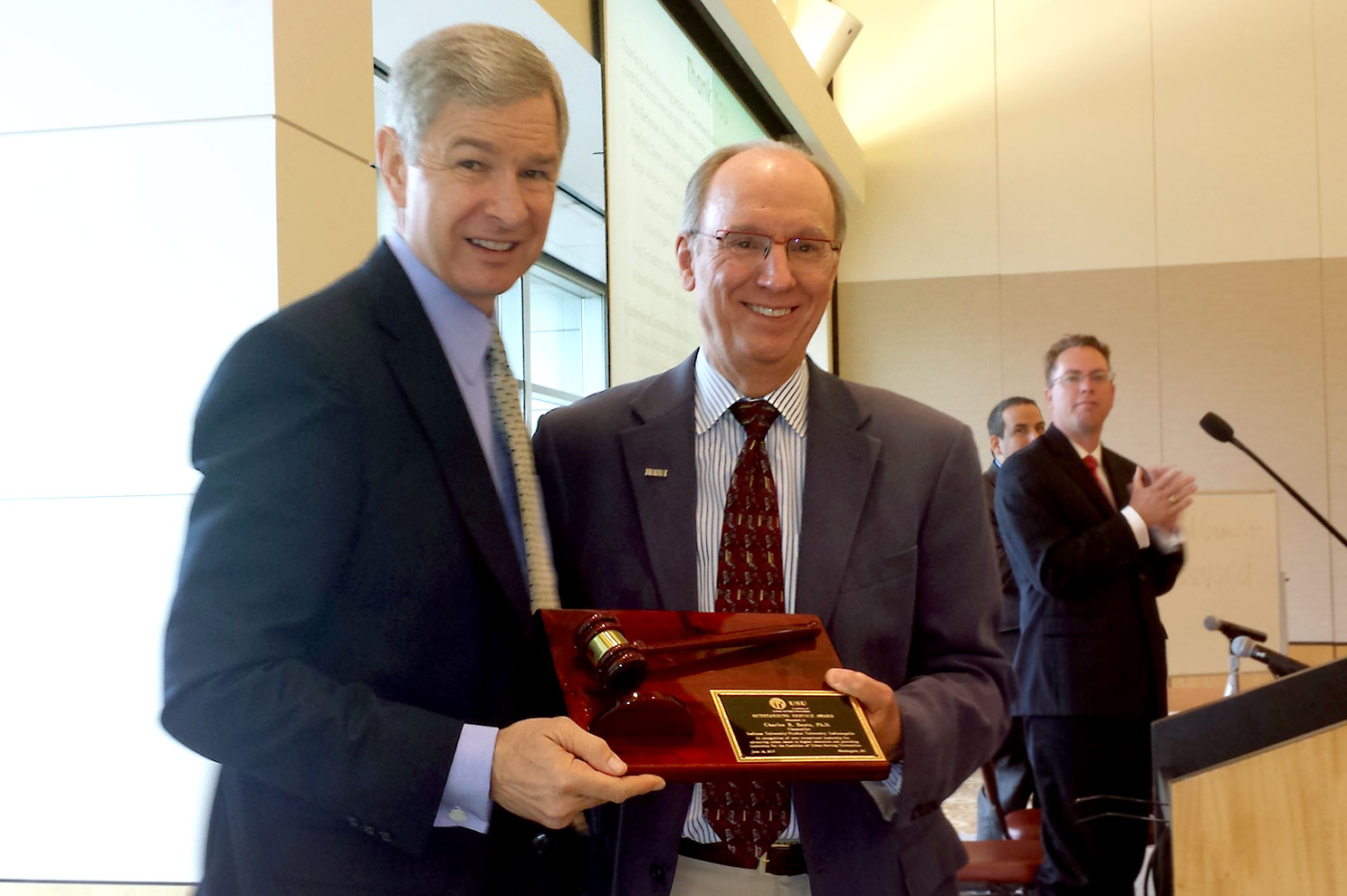 Chancellor Bantz receives a plaque from Mark Becker, president of Georgia State University.